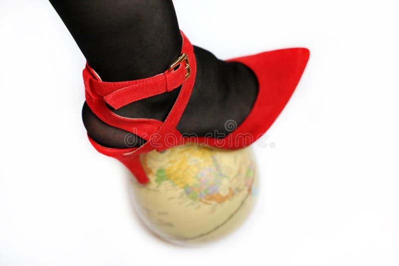 Kvinnlig dominans och ledarskap, lägger benen på ryggen i sko på den höga hälet på jordklotet som isoleras på vit Begrepp av kvin fotografering för bildbyråer