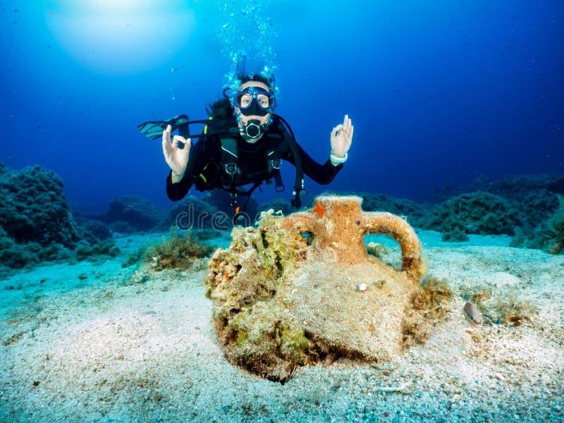 Kvinnlig dykare som är främst av ett forntida, sjunket i det Aegean havet arkivbilder