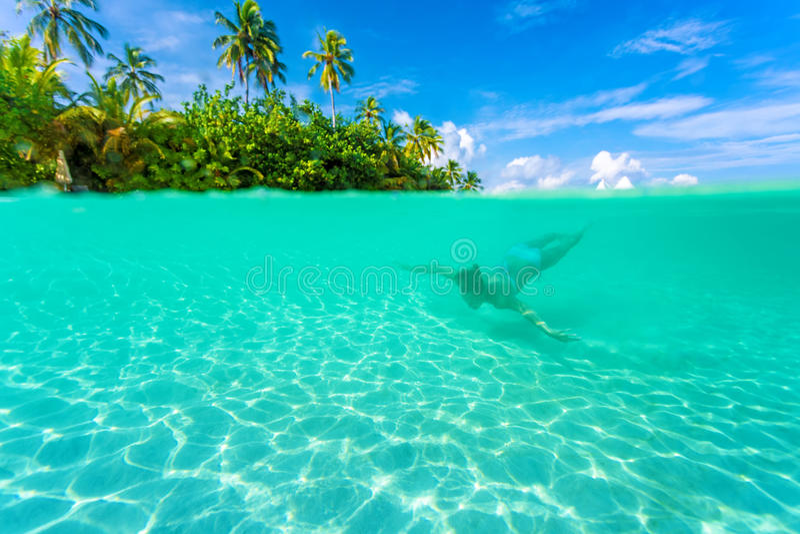 Kvinnlig dykning nära den exotiska ön royaltyfri bild