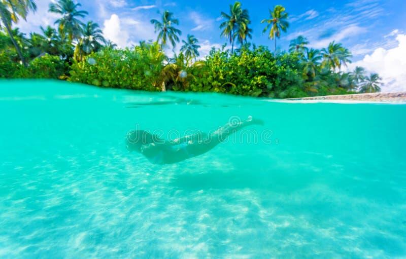 Kvinnlig dykning nära den exotiska ön fotografering för bildbyråer