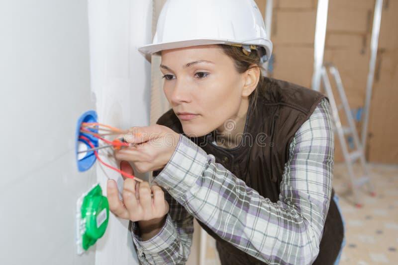 Kvinnlig elektriker som kontrollerar kablar royaltyfria bilder