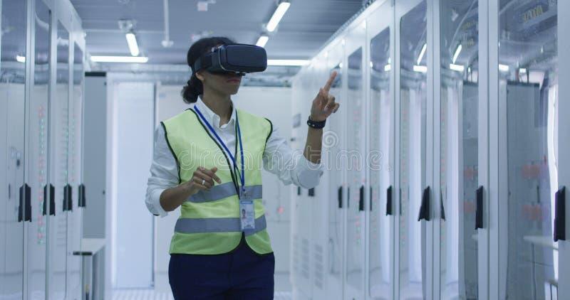Kvinnlig elektrisk arbetare som använder en VR-hörlurar med mikrofon royaltyfria bilder