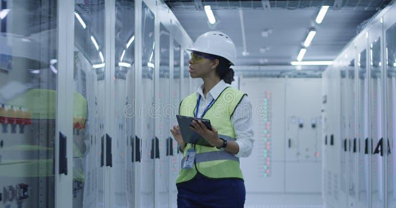 Kvinnlig elektrisk arbetare som utför en kontroll arkivfoton