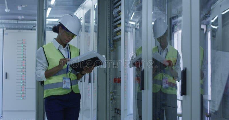 Kvinnlig elektrisk arbetarläsningskrivbordsarbete fotografering för bildbyråer