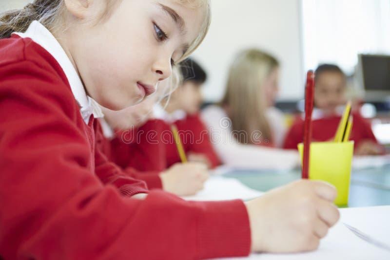 Kvinnlig elementär elev som arbetar på skrivbordet arkivfoton