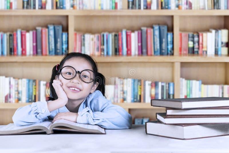 Kvinnlig elementär student som studerar i arkiv arkivfoton