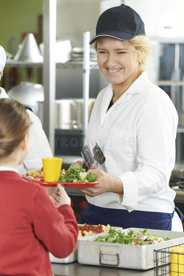 Kvinnlig elev i skolakafeterian som tjänas som lunch av matställeLa arkivbild