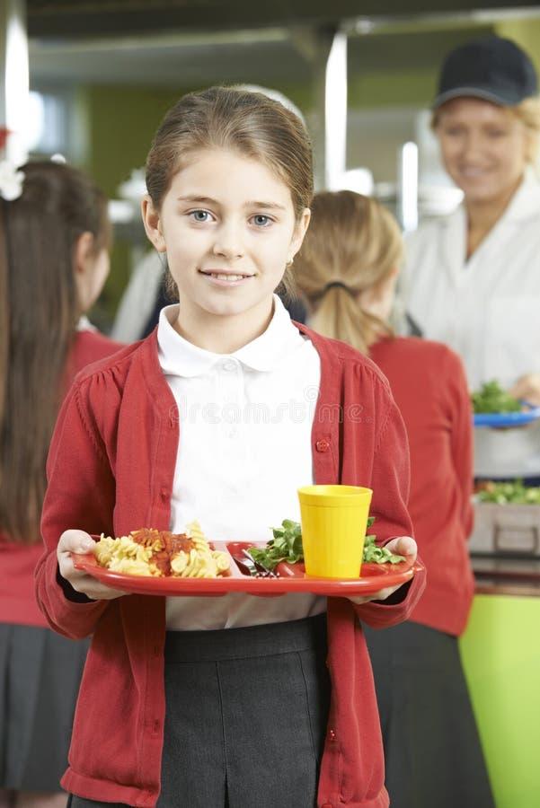 Kvinnlig elev med sund lunch i skolakafeteria royaltyfri bild