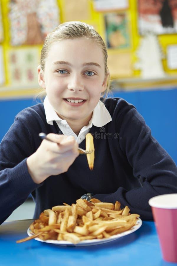 Kvinnlig elev som äter sjuklig skolalunch arkivfoto
