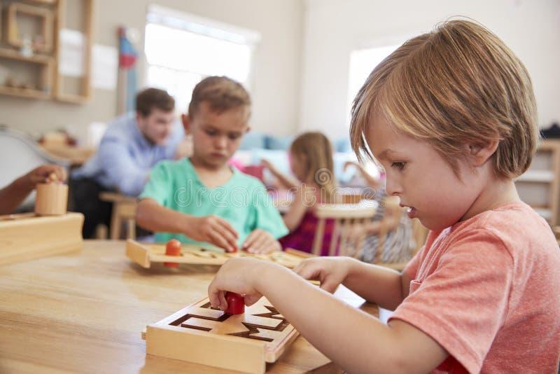 Kvinnlig elev som arbetar på tabellen i den Montessori skolan royaltyfria bilder