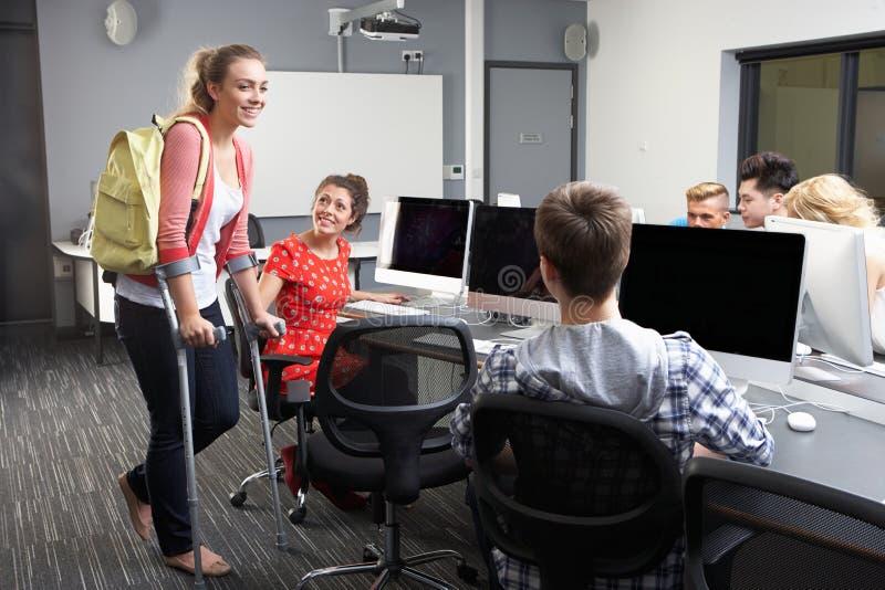 Kvinnlig elev som går på kryckor i datorgrupp royaltyfria foton
