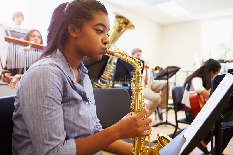 Kvinnlig elev som spelar saxofonen i högstadiumorkester royaltyfri fotografi