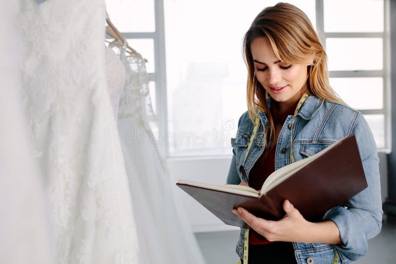 Kvinnlig entreprenör i brud- klädlager royaltyfri foto