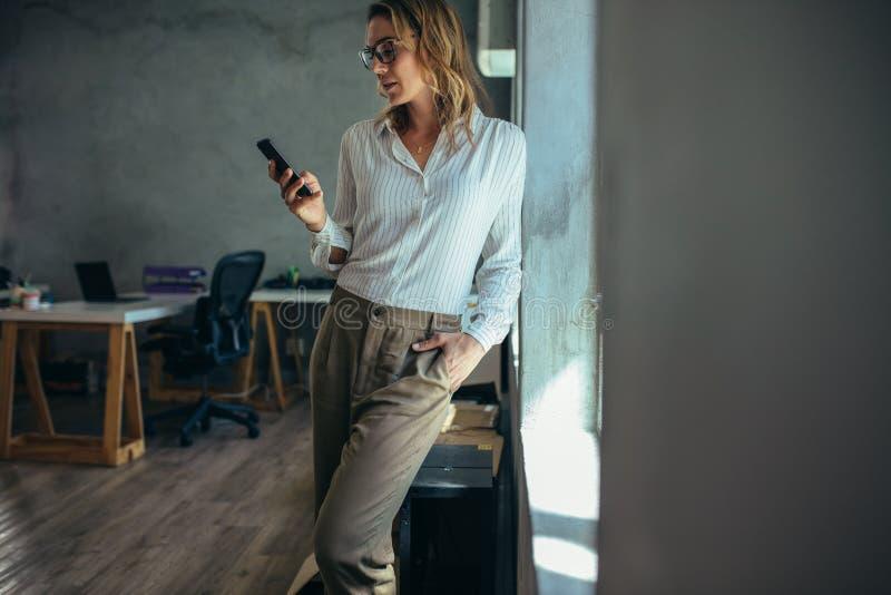 Kvinnlig entreprenör som använder mobiltelefonen arkivfoto