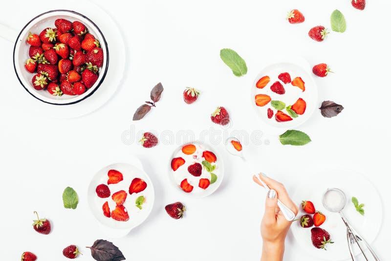 Kvinnlig \ 'för s-handinnehav sked över en bunke av jordgubbeglass arkivfoton
