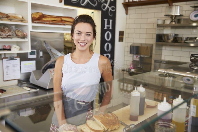Kvinnlig företagsägare bak räknaren på en smörgåsstång royaltyfria foton