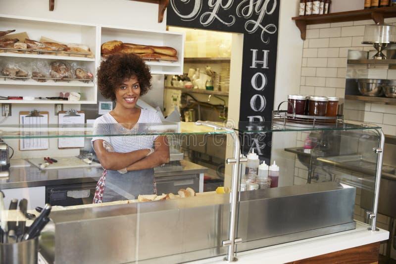 Kvinnlig företagsägare bak räknaren på en smörgåsstång royaltyfri foto