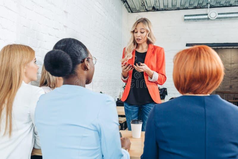 Kvinnlig försäljningskonsulent som berättar om nytt gods till unga affärskvinnor fotografering för bildbyråer