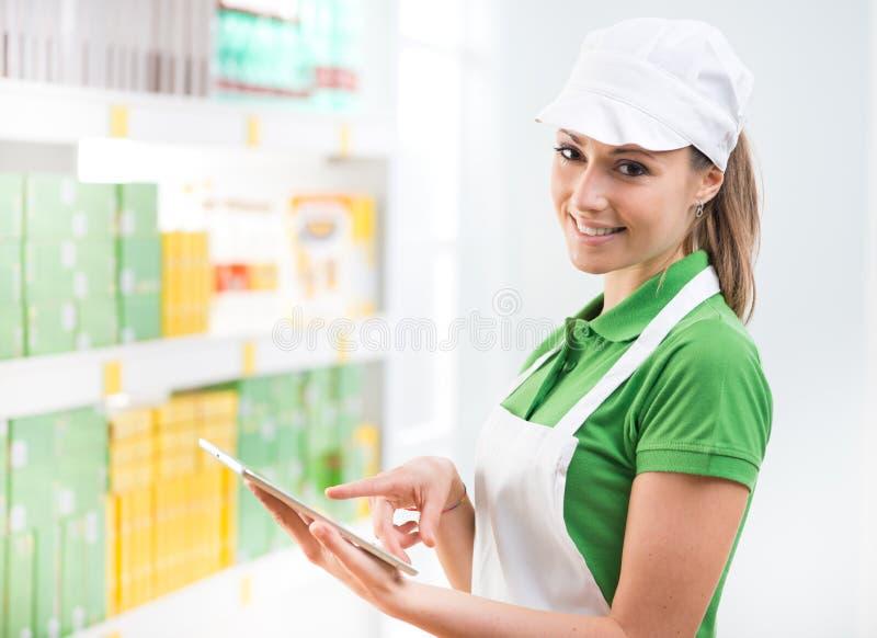Kvinnlig försäljningskontorist med minnestavlan på supermarket arkivfoto