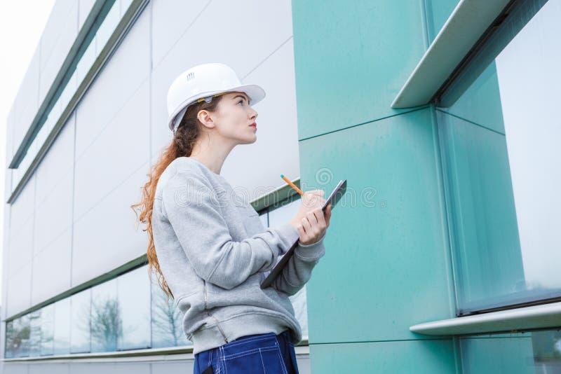 Kvinnlig fabriks- jobbare som rymmer utomhus skrivplattan fotografering för bildbyråer