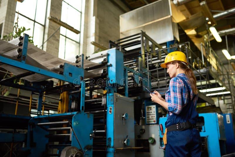 Kvinnlig fabriksarbetare Overseeing Production arkivfoton