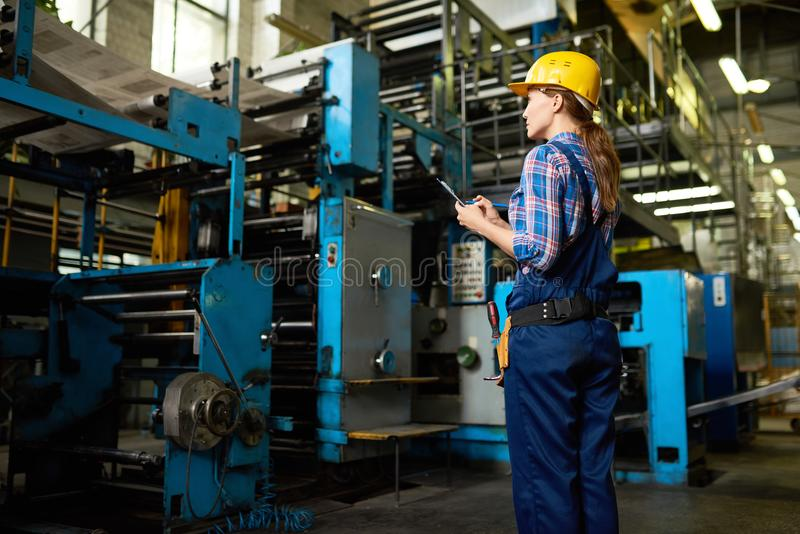 Kvinnlig fabriksarbetare Supervising Quality av produktion royaltyfri foto