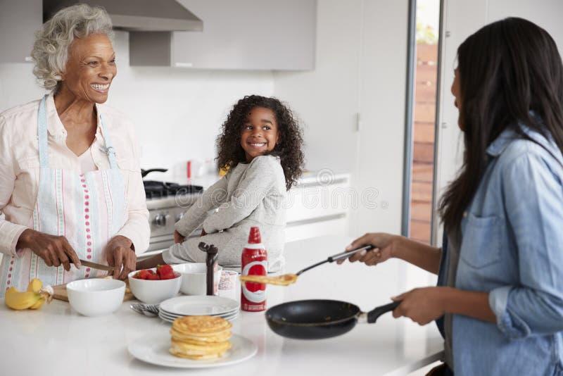 Kvinnlig familj för mång- utveckling i kök hemma som tillsammans gör pannkakor arkivfoto