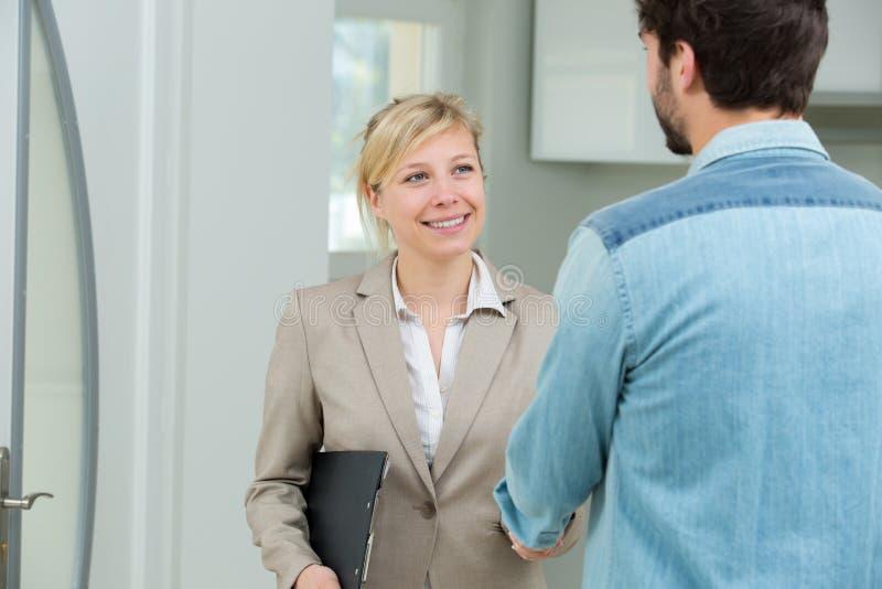 Kvinnlig fastighetsm?klare som v?lkomnar den manliga klienten till egenskapen royaltyfria foton