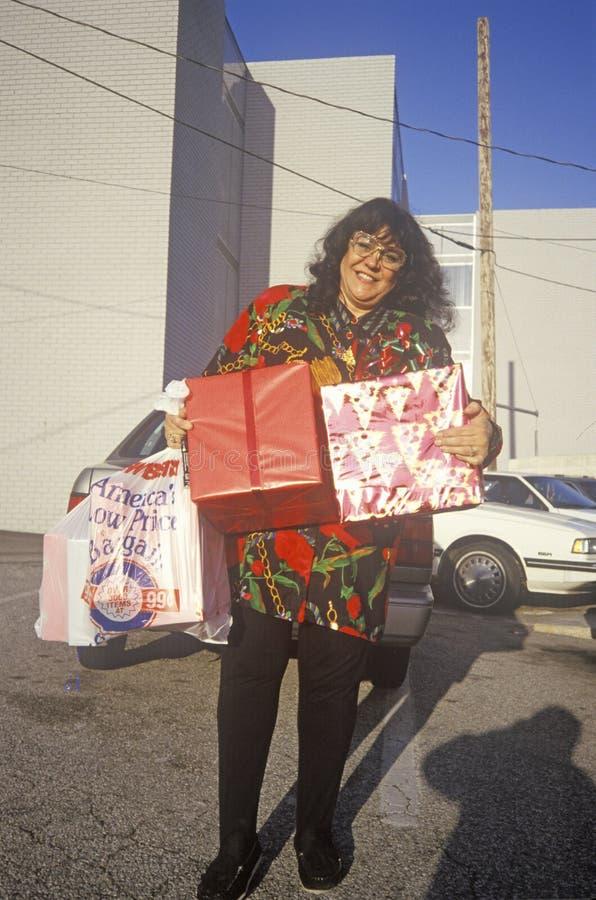 Kvinnlig ferieshoppare med slågna in packar som lämnar lagret, Los Angeles, CA arkivfoton