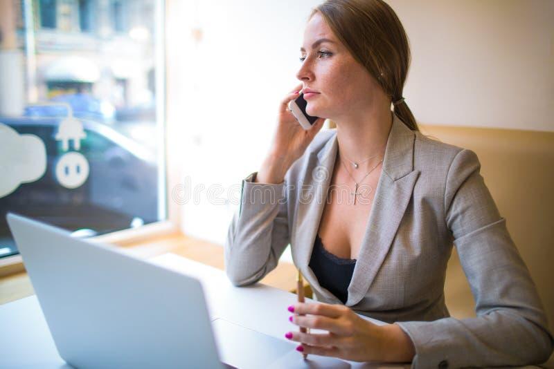 Kvinnlig finansiär som har smartphonekonversation under arbetsavbrott arkivfoto
