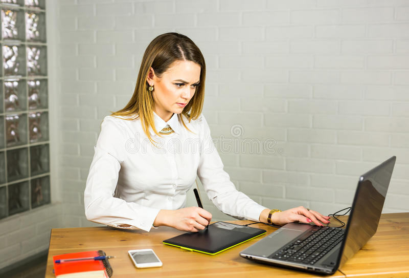 Kvinnlig formgivare i regeringsställning som arbetar med den digitala grafiska minnestavlan och bärbara datorn Fotografiretoucher royaltyfri fotografi