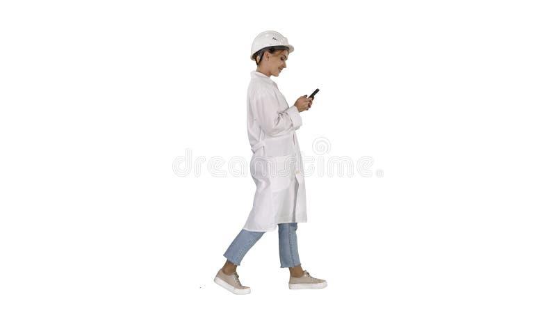 Kvinnlig forskare Using Smartphone Walking på vit bakgrund arkivbild