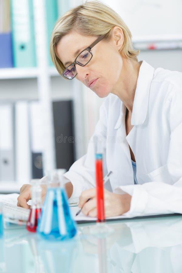 Kvinnlig forskarehandstilrapport p? vetenskapsexperiment arkivfoto