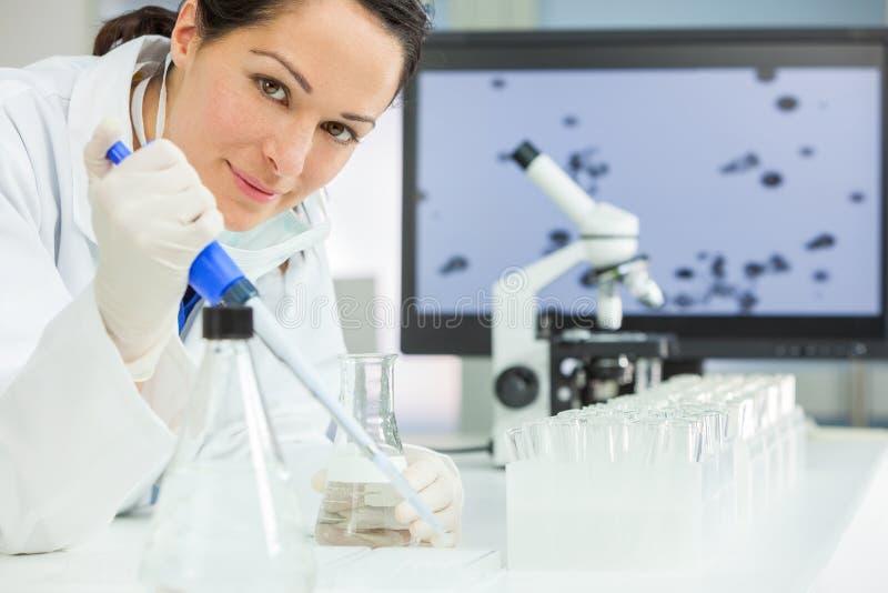 Kvinnlig forskningforskare With Pipette & flaska i laboratorium arkivbild