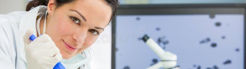 Kvinnlig forskningforskare With Pipette & flaska i laboratorium arkivfoto