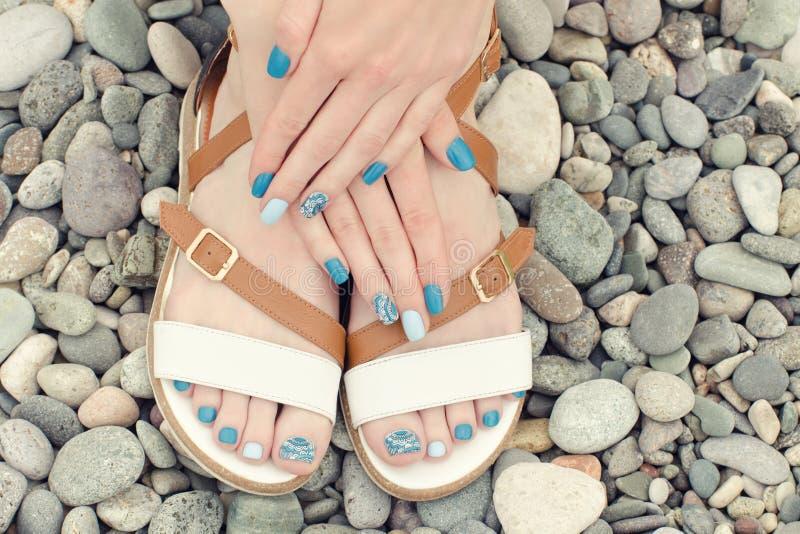 Kvinnlig fot i sandaler och händer med en blå manikyr på kiselstenar Top beskådar royaltyfri bild