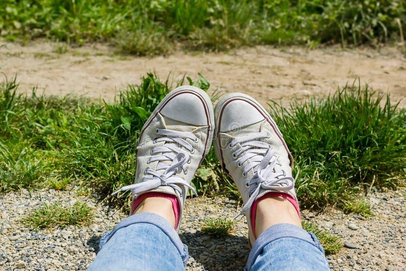 Kvinnlig fot i vit kanfasgymnastikskor och jeans i ett gräs royaltyfria foton