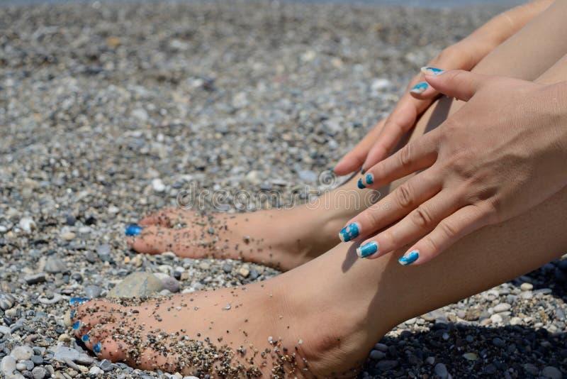 Kvinnlig fot och händer på stranden fotografering för bildbyråer
