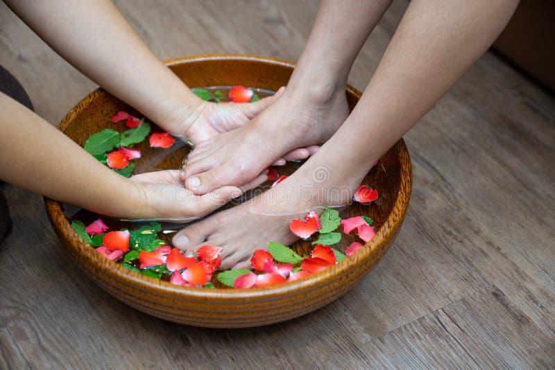 Kvinnlig fot på brunnsortpedikyrtillvägagångssättet, Spa fotmassage, massage av kvinnas fot i brunnsortsalong, skönhetbehandlingb arkivfoto