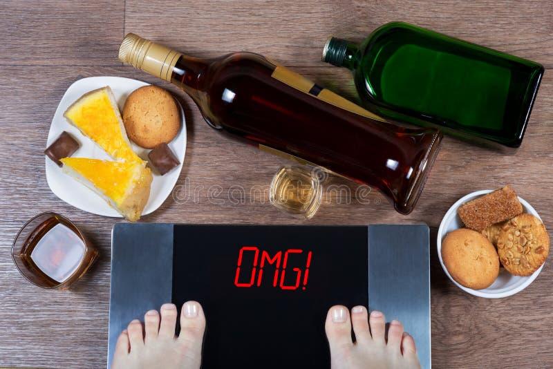 Kvinnlig fot på digital våg med ordomg på skärmen Flaskor och exponeringsglas av alkohol, plattor med söt mat arkivbilder