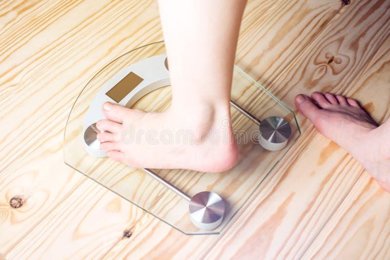 Kvinnlig fot som står på elektronisk våg för viktkontroll royaltyfri fotografi