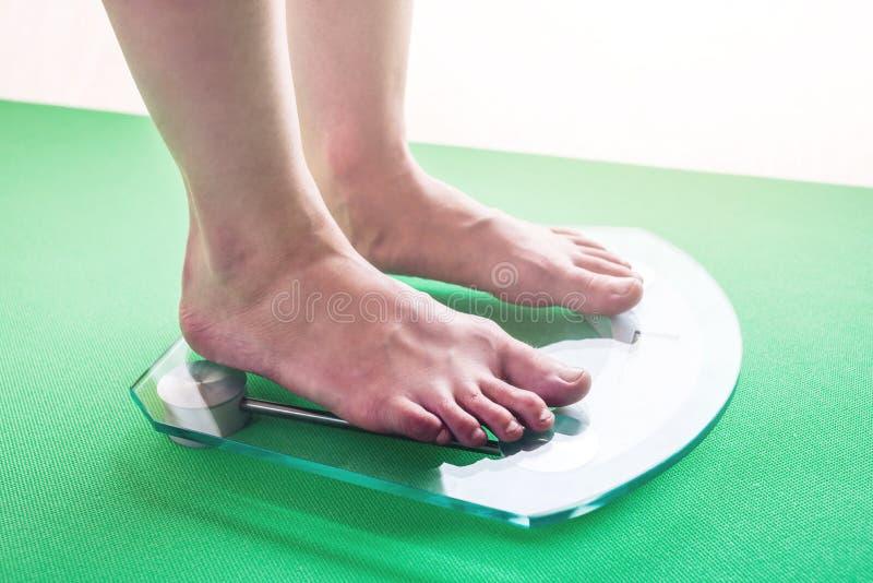 Kvinnlig fot som står på elektronisk våg för viktkontroll Begrepp av bantning- och viktförlust arkivfoton