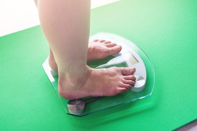 Kvinnlig fot som står på elektronisk våg för viktkontroll Begrepp av bantning- och viktförlust royaltyfri bild