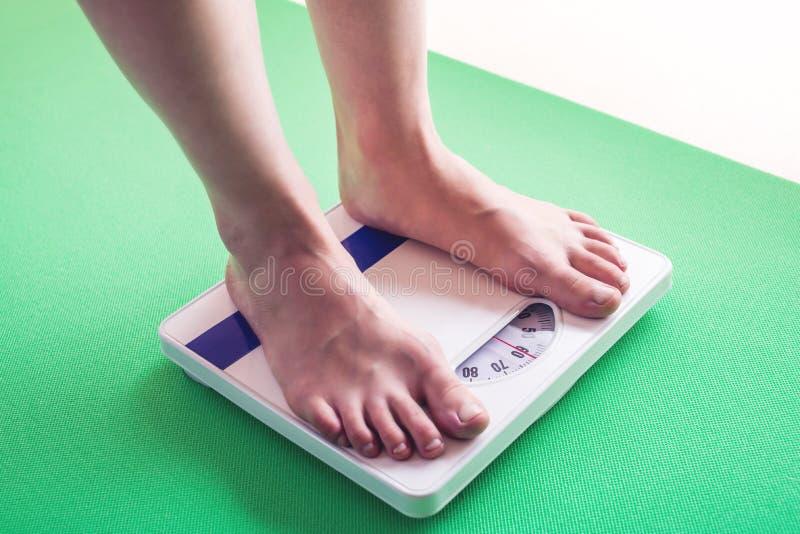 Kvinnlig fot som står på mekanisk våg för viktkontroll Begrepp av bantning- och viktförlust arkivfoton