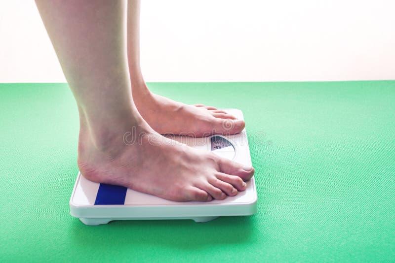 Kvinnlig fot som står på mekanisk våg för viktkontroll Begrepp av bantning- och viktförlust royaltyfri foto