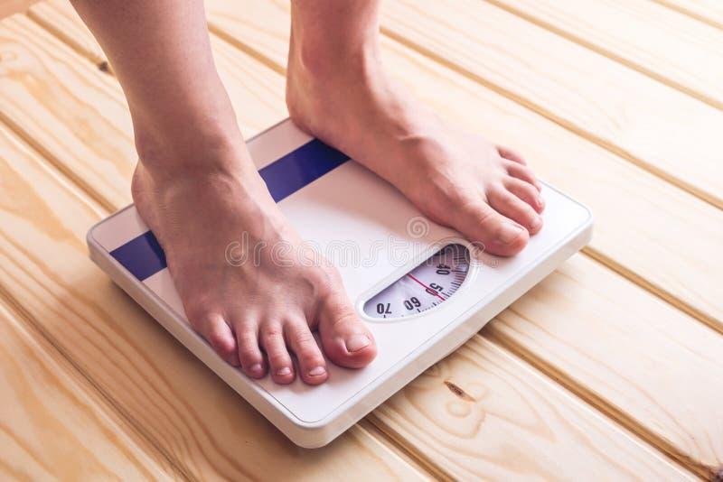 Kvinnlig fot som står på mekanisk våg för viktkontroll på träbakgrund Begrepp av bantning- och viktförlust arkivfoton
