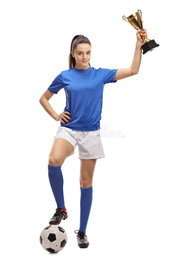 Kvinnlig fotbollspelare med en fotboll och en guld- trofé arkivbild