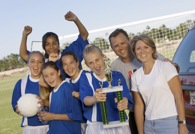Kvinnlig fotbollspelare med vänner och förälderinnehavtrofén royaltyfria bilder