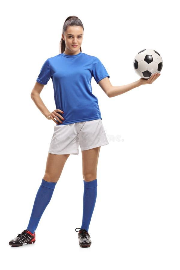Kvinnlig fotbollspelare som rymmer en fotboll royaltyfria bilder