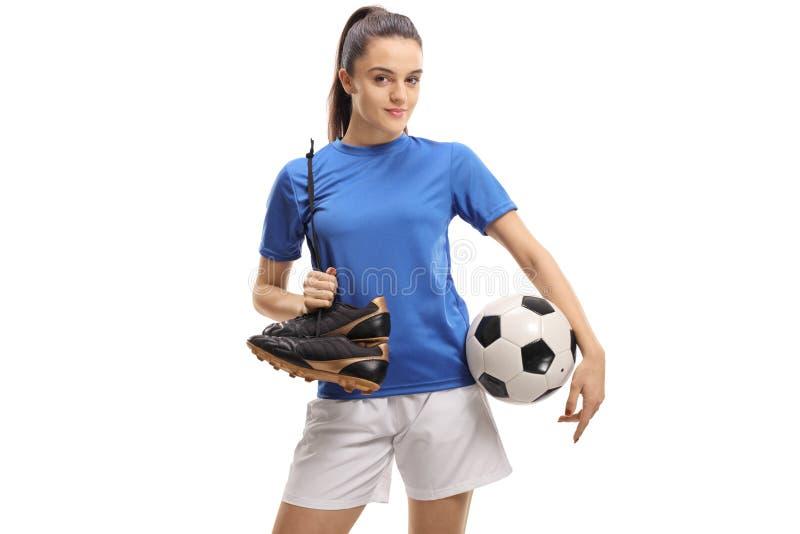 Kvinnlig fotbollspelare som rymmer ett par av dubbar och en fotboll royaltyfri bild